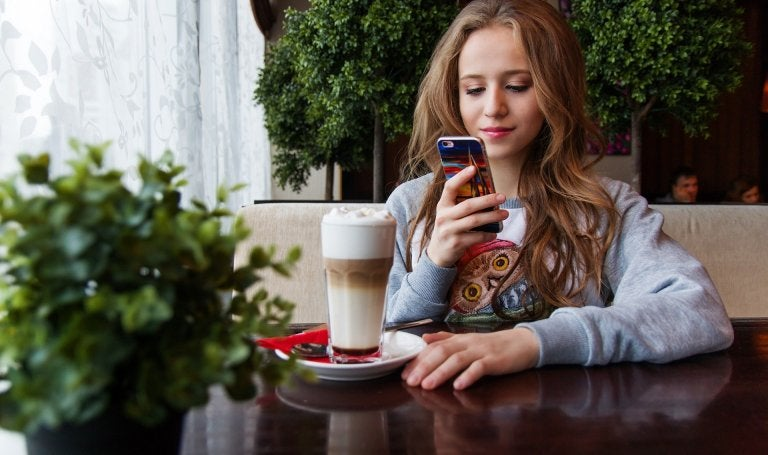 young girl sits at cafe table with drink while looking at her cell phone