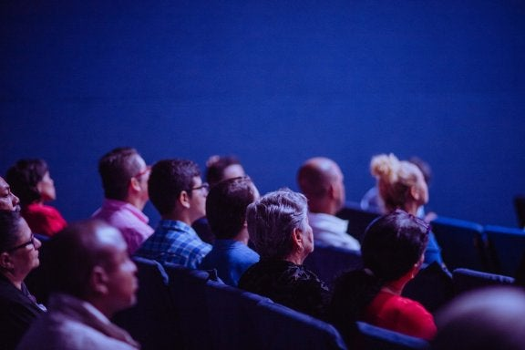 group of people sitting in a theater facing a movie screen