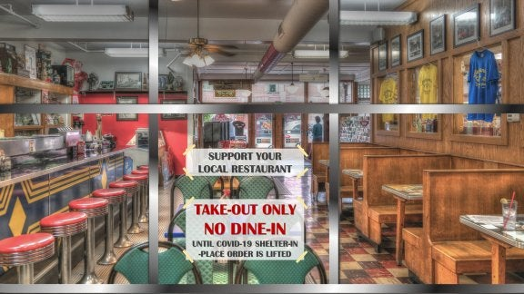 restaurant with sign on the door that says due to pandemic they are doing take-out only