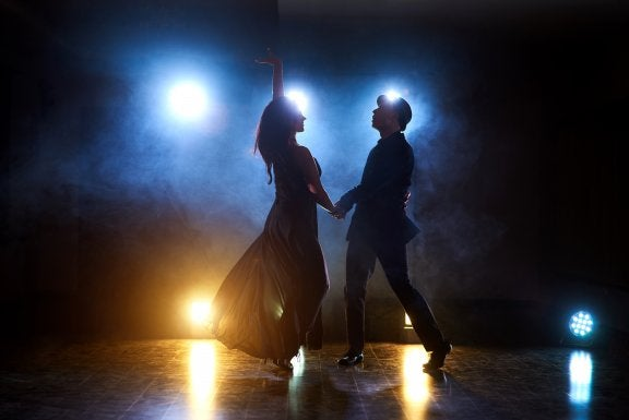 couple dance on stage backlit with lights