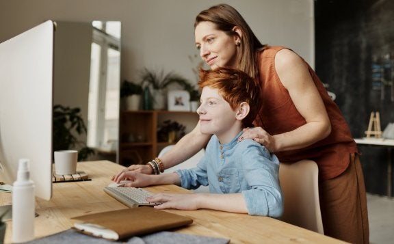 a parent looks at the computer screen with child over the shoulder