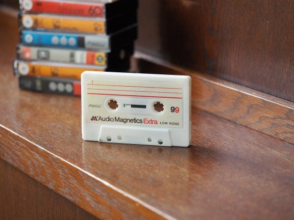 photo of cassette standing upright on table with stack of cassette cases behind