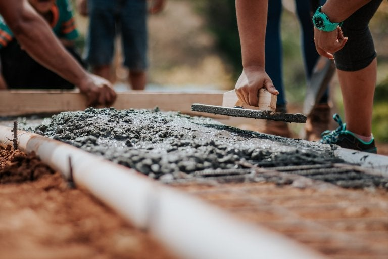 group of people laying concrete foundation
