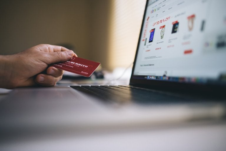 image of person holding credit card next to laptop with shopping site